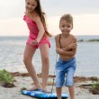 Kids playing with surfing board on beach — Stock Photo