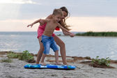 Sister teaching her brother how to surf — Stock Photo