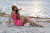 Cute young girl in hat sitting on the beach — Stock Photo