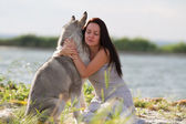 Young woman with alaskan malamute dog — Stock Photo