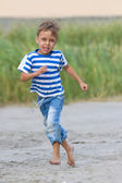 Funny little boy running outdoors — Stock Photo