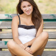 Smiling teen girl on a bench — Stock Photo
