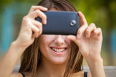 Smiling girl taking photo with smartphone — Stock Photo
