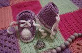 Nice baby's bootees on crochet blanket — Stock Photo