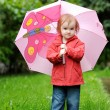 Foto Stock: Adorable toddler girl at rainy day in autumn