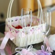 Stock Photo: A pair of wedding glasses, basket and a ring pillow