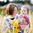 Young mother and her toddler girl in autumn — Stock Photo