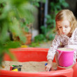 Little girl playing in a sandbox — Stock Photo #13725040