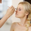 Young beautiful bride applying wedding make-up — Stock Photo #13725076