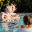 Father and daughter swimming in pool - Stock Photo