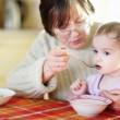 Büyükanne küçük bebek torunu besleme — Stok fotoğraf