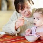 Grandmother feeding her little baby granddaughter — Stock Photo