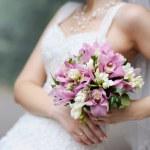 Bride holding pink wedding flowers bouquet — Stock Photo #13725195