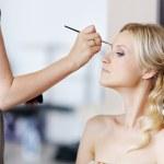 Young beautiful bride applying wedding make-up — Stock Photo #13725250