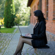 Young lady sitting on stone steps with a notebook — Stok fotoğraf