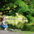 Adorable girl sitting by the water — Stock Photo #13725280