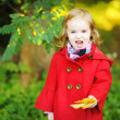 Little girl in bright red coat at autumn — Stock Photo #13725303