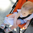 Little girl sitting in a stroller — Stock Photo