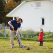 A man shovels a hole in the yard — Stock Photo