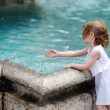 Stock Photo: Funny child having fun by city fountain