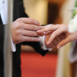 Groom putting a ring on bride's finger — Foto Stock