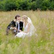 Bride and groom sitting in a meadow — Photo