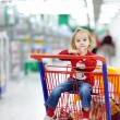 Adorable toddler sitting in shopping cart — Stock Photo #13725926