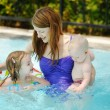 Mother and two daughters swimming in pool - Stock Photo