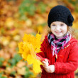 Little girl in bright red coat at autumn — Stock Photo