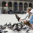 Stock Photo: Adorable little girl and her father feeding pigeons
