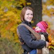 Young mother and her baby in a carrier — Stock Photo