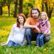Beautiful expecting family in autumn park — Stock Photo