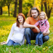 Stock Photo: Beautiful expecting family in autumn park