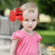 Adorable toddler girl with a hibiscus — Stock Photo