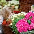 Adorable little girl smelling flowers — Stock Photo