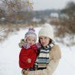 Little winter baby girl and her young mother — Stock Photo #13726442