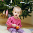 Toddler girl sitting under the Christmas tree — Stock Photo
