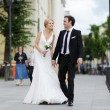 Bride and groom walking in town — Stock Photo #13726662