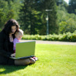 Young lady with a baby and a notebook in a park — Stock Photo