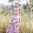Adorable girl in a beautiful floral dress — Stock Photo #13726982