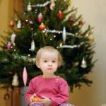 Toddler girl sitting under the Christmas tree — Stock Photo