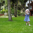 Adorable toddler girl playing with a grass — Stock Photo