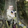Little toddler girl sitting at a tree branch — Stock Photo