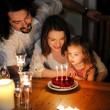 Happy family celebrating daughter's third birthday - Stock Photo