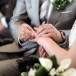Groom putting a ring on bride's finger — Stok fotoğraf