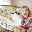 Stock Photo: Little funny girl in pajamas on sunny morning