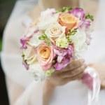 Bride holding beautiful wedding flowers bouquet — Stock Photo