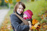 Jovem mãe e seu bebê em um portador — Fotografia Stock