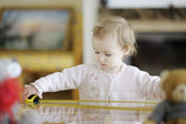 Toddler girl plaing with a measuring tape — Stock Photo