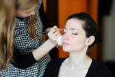 Young beautiful woman applying wedding make-up — Stock Photo